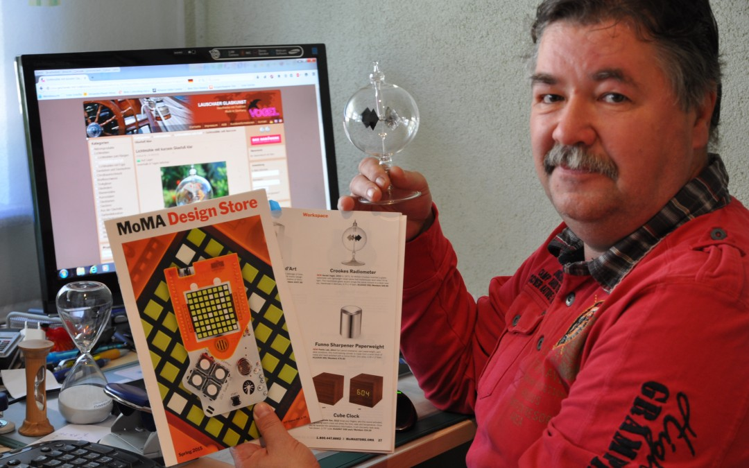 Gerald Vogel der Glasbläserei mit Produktkatalog und gefertigter Glaskugel